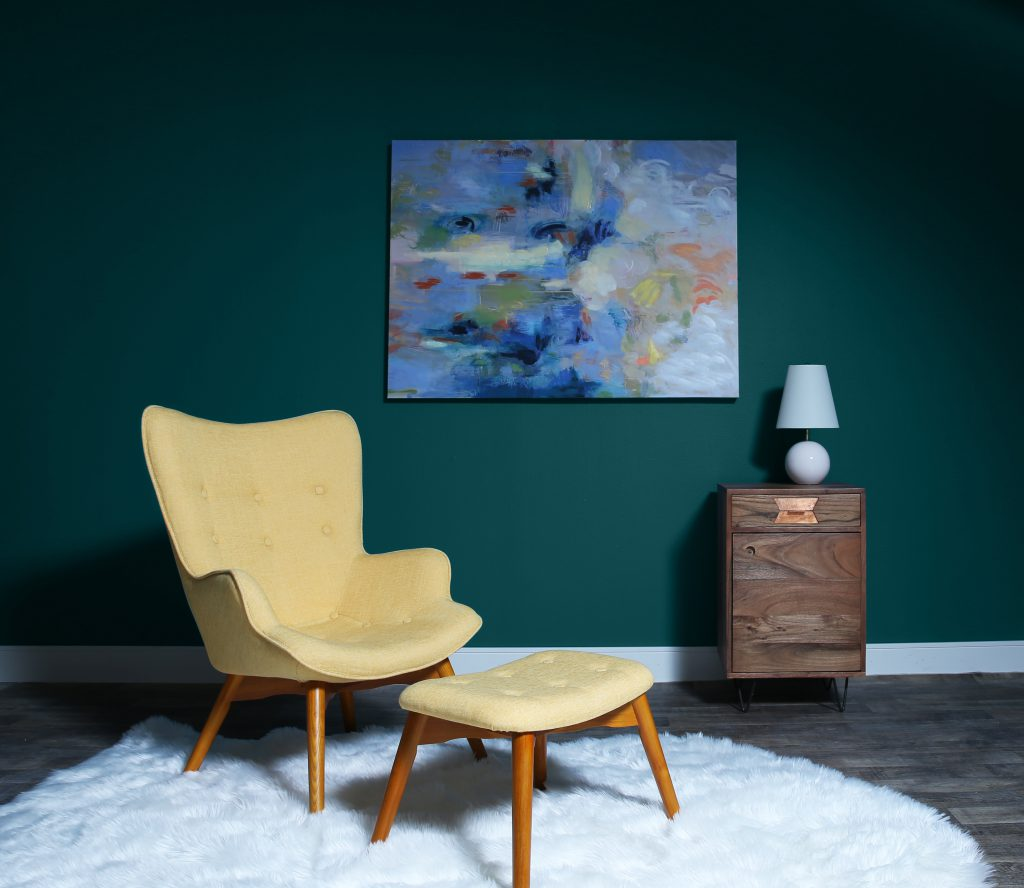 A mid century modern sitting room in front of a wall painted in Antigua M460-7. There is an abstract piece of art hanging from the wall.