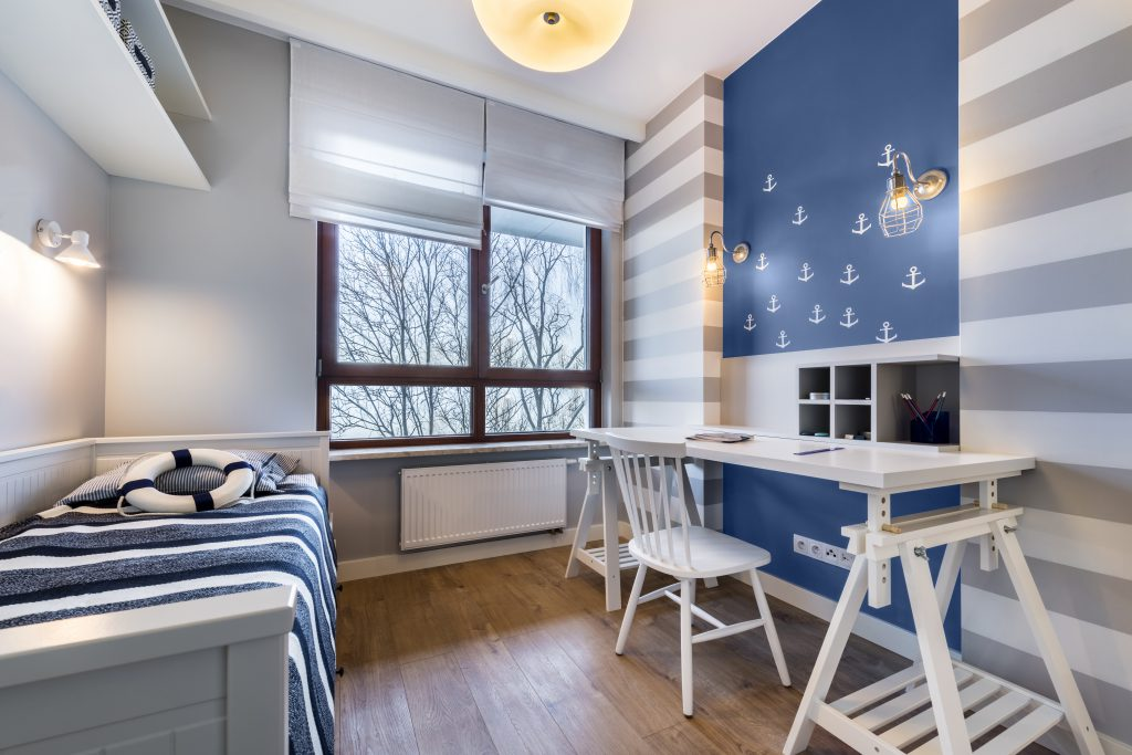 A nautical theme teen room showcasing a solid gray wall, two white and gray walls and a blue accent wall.