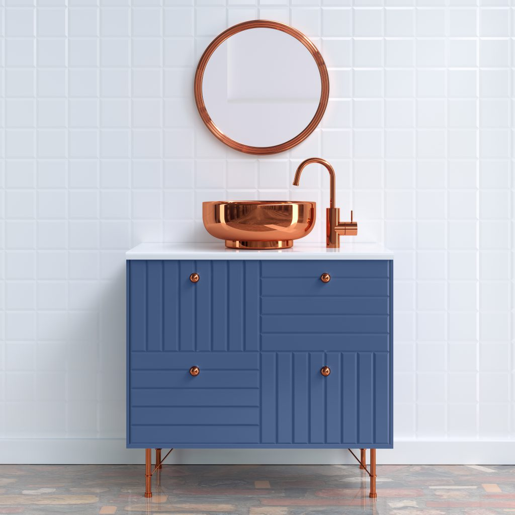An all white-tiled bathroom with a blue vanity and metallic copped hardware.