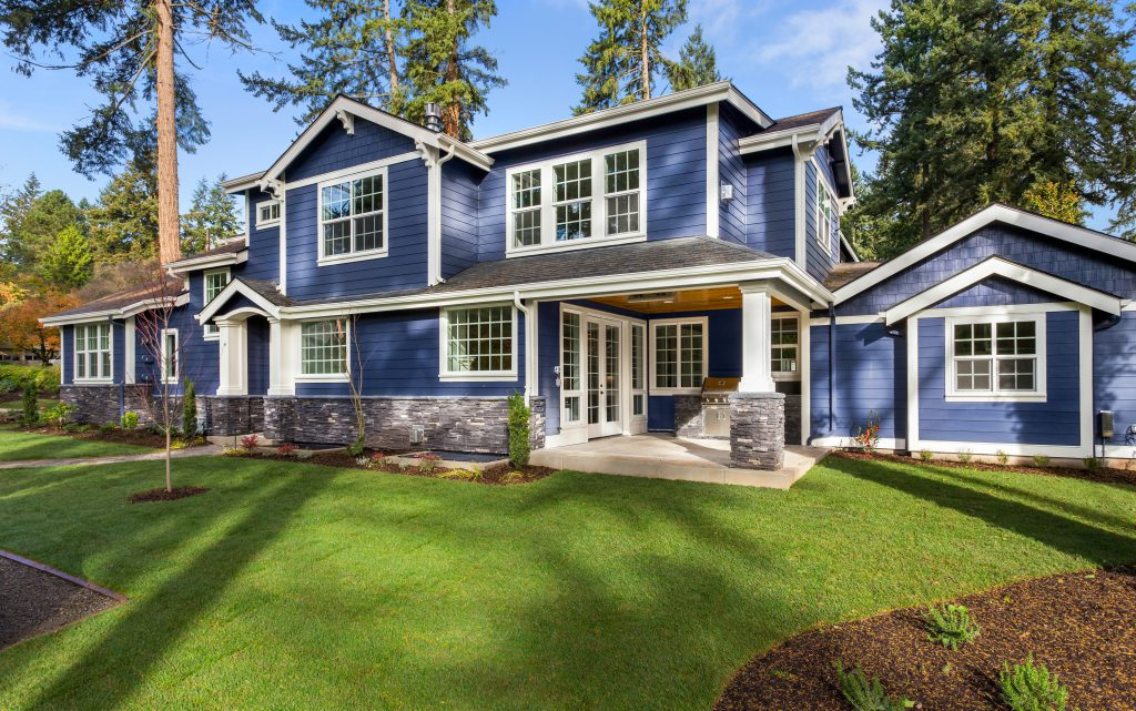 A large all american suburban home showcasing siding painted in blue color called Optimum Blue.