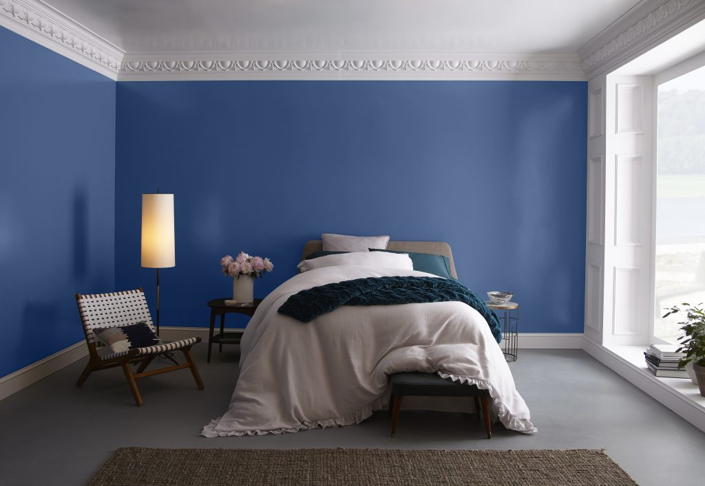 A blue bedroom showcasing large wall-sized window and fluffy, comfy bed.  White painted woodwork including ornate crown molding.