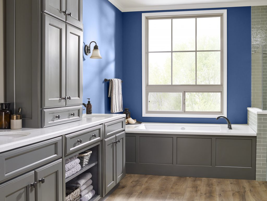 A well lit large blue bathroom with tub and a lot of gray  storage cabinetry.