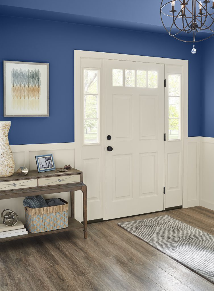 A nice two-toned entryway with a lot of crisp white wood work and  walls painted in blue color called Optimum Blue.