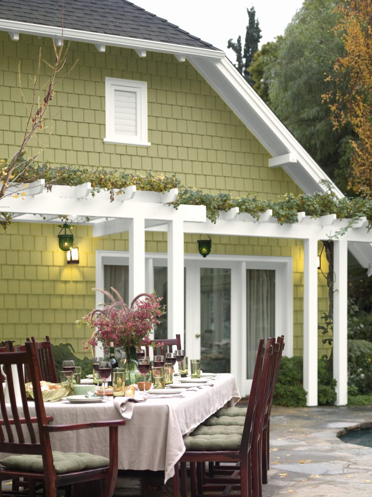 An exterior home painted in Back to Nature. The patio is set up with a long table for a large dinner party.