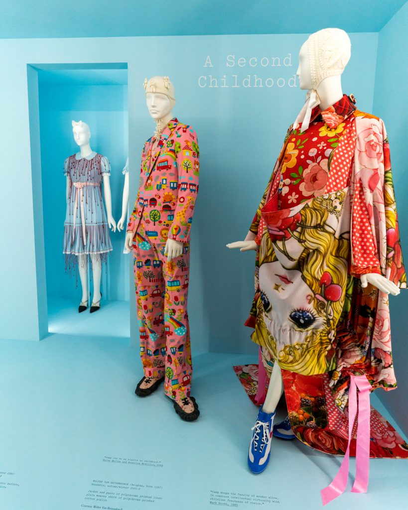A photo taken at the Met Museum of store manicans dressed in colorful attire.