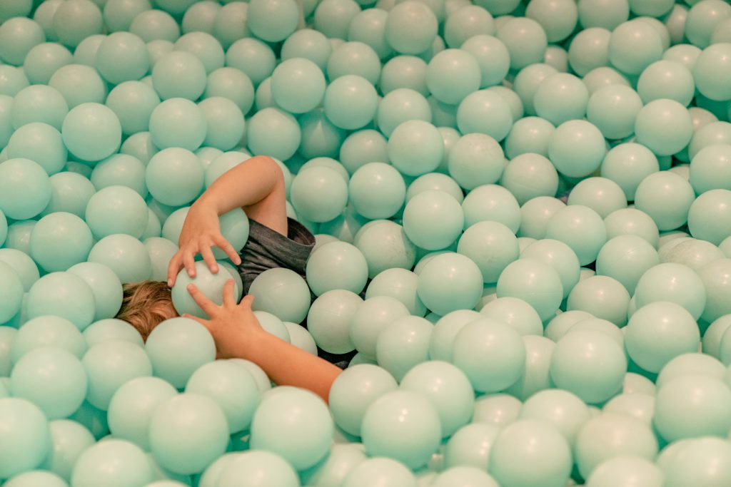 A photo taken at the Color Factory in New York with a boy surrounded by a bunch of green plastic balls.