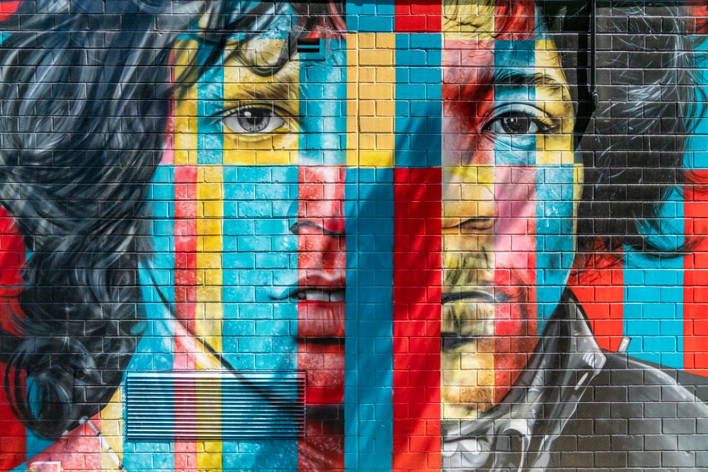 Wall art found on the streets of NEW York City This is a mural of two half faces with color blocking in red, blue and yellow.