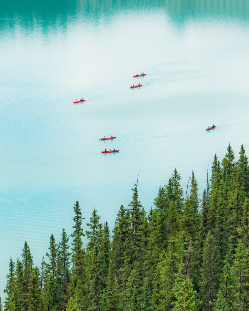 A helicopter view of a lake with red canoes in the water.