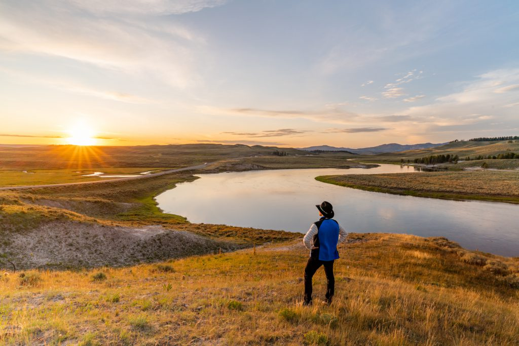 A man standing on a hill with a view of a lake and the sun setting.
