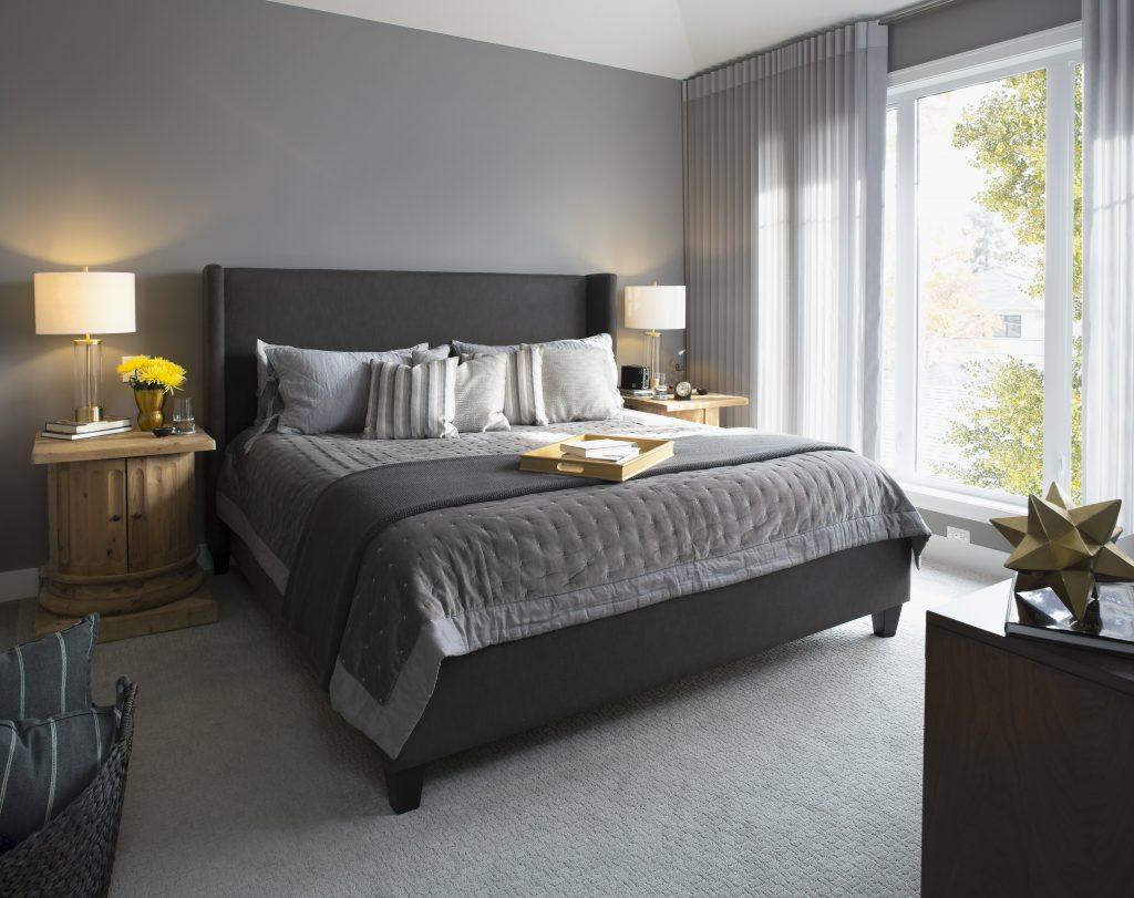 Elegant, modern bedroom showcase various gray tones.   An upholstered gray bed dressed with simple yet  elegant bedding.