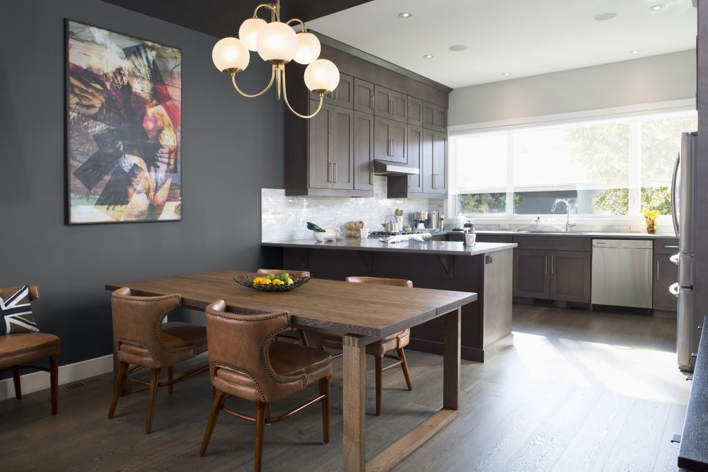 An open floor plan featuring a kitchen and dining area, painted in Graphic Charcoal.  A kitchen with plenty of cabinet storage. A dining area with warm toned wood and leather furniture.
