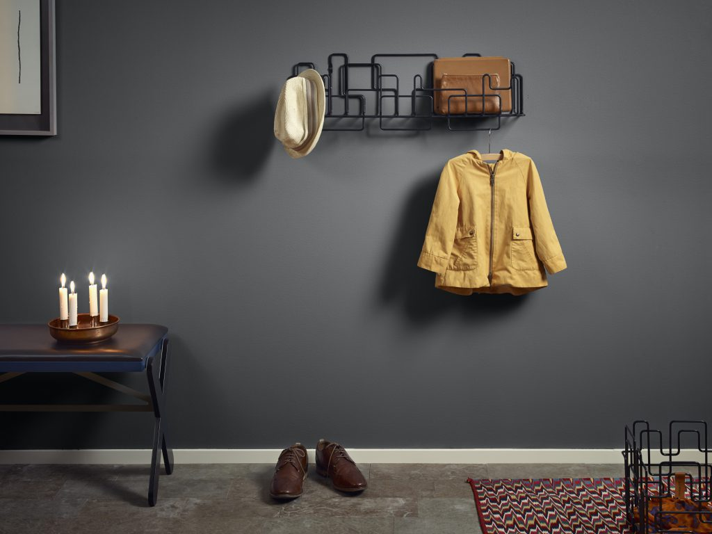 A modern hallway painted in a gray color called Graphic Charcoal. A metal coat rack shaped in an artistic wall statement. Several warm toned furniture and decorative elements.
