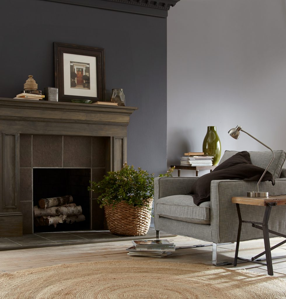 A living room featuring a fireplace with an antiqued wood finish mantle, the wall is painted in dark gray color called Graphic Charcoal. A mix of decorative elements including stacks of books, tin box, wall artwork, ceramic vases and plant in a basket.