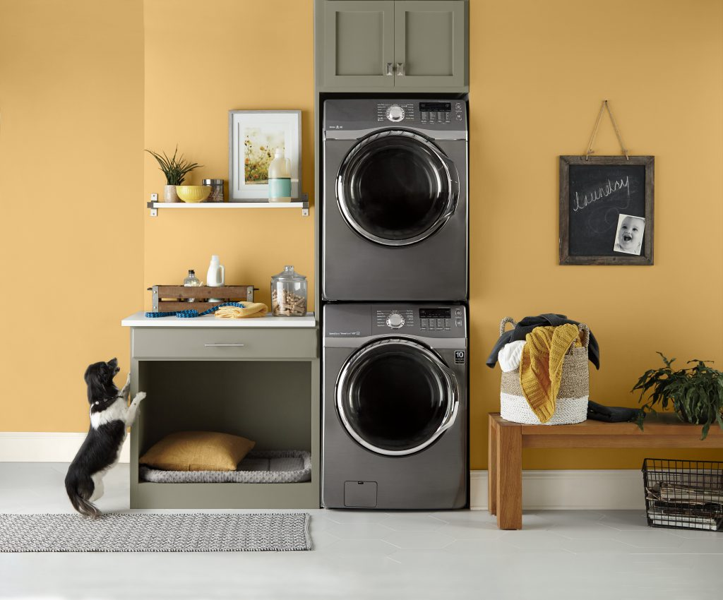 This is a laundry painted in Charismatic. There are stainless steel washer and dryer stacked on top one each other.  This laundry room is also a doggy room. There is a half dresser with only one drawer and the bottom is open for doggy, and his bed.  There are decorative items as well in this room.