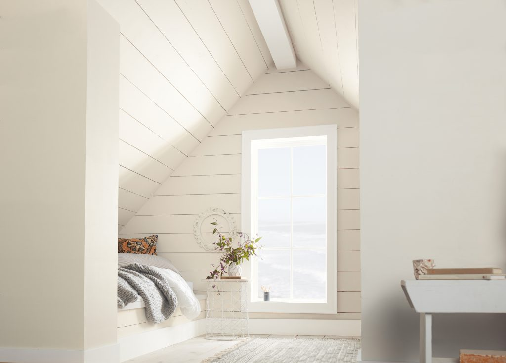 A well light up attic that was made into a small room.  Making it even more lively the walls are painted in Painter's White. There are cathedral ceilings which are slanted triangle ceiling.  The bed is in a small nook area and there is a side table.