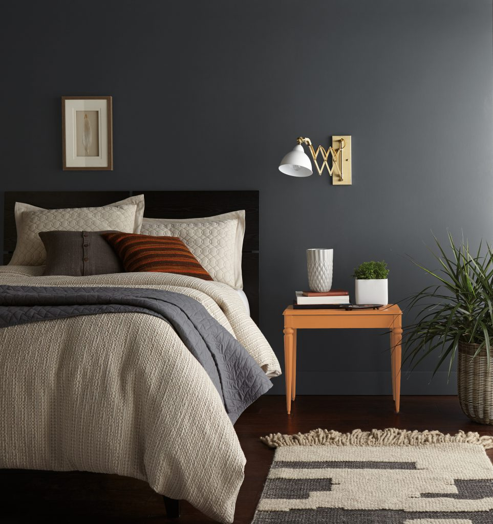A bedroom with Graphic Charcoal painted walls. A cozy dark wood bed  made with multi-textural bedding.