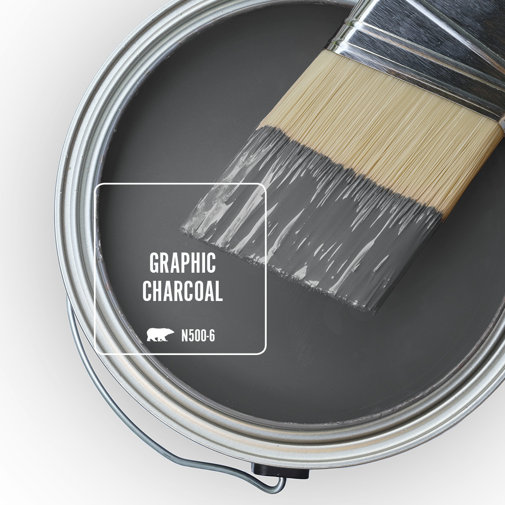 An open paint can overview featuring wet paint tinted in a dark gray color called Graphic Charcoal.