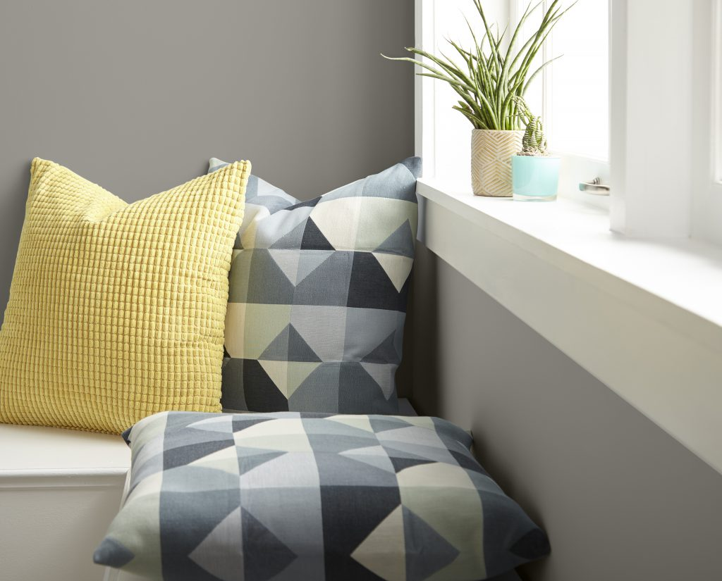 Detail photo of geometric pillows in gray tones and a yellow pillow. This image also shows a window sill with small plants.