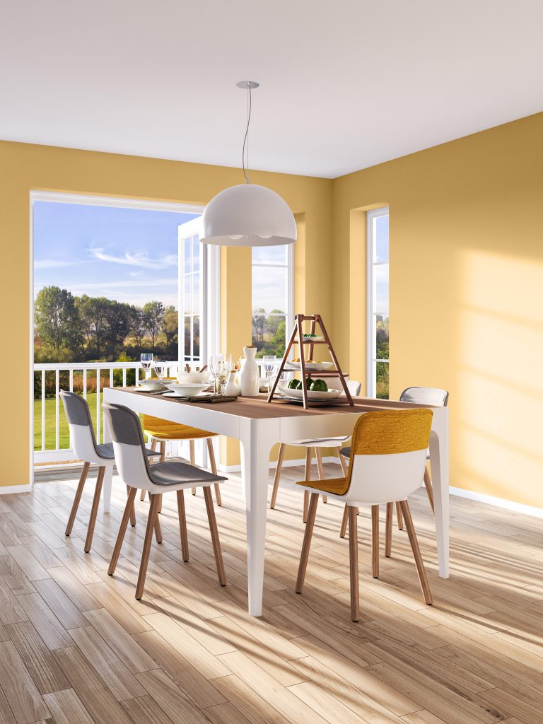 A indoor modern dining area with a beautiful outside view. A table facing the outdoors and set for a meal and Walls painted in yellow color called Charismatic.