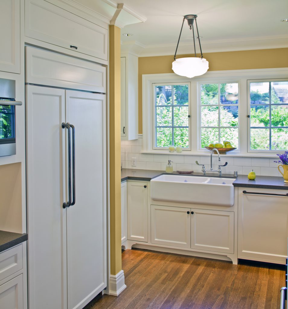 A kitchen with white painted cabinets and abundant natural light.  Walls painted in yellow color called Charismatic.