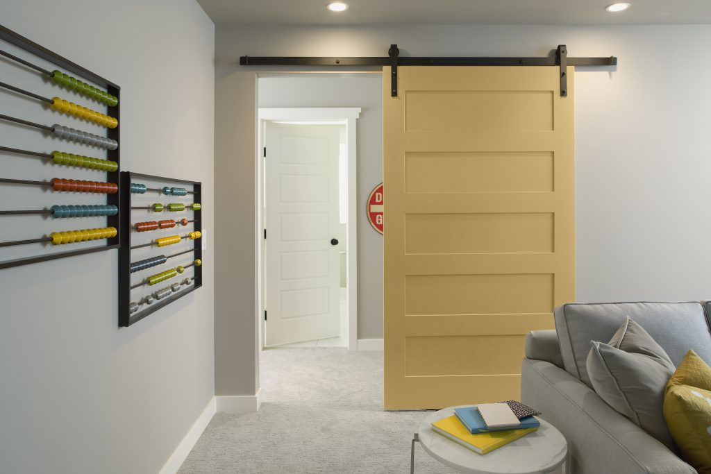 A multi-purpose sitting and  a play space area for kids featuring a sliding farmhouse door painted in yellow color called Charismatic.