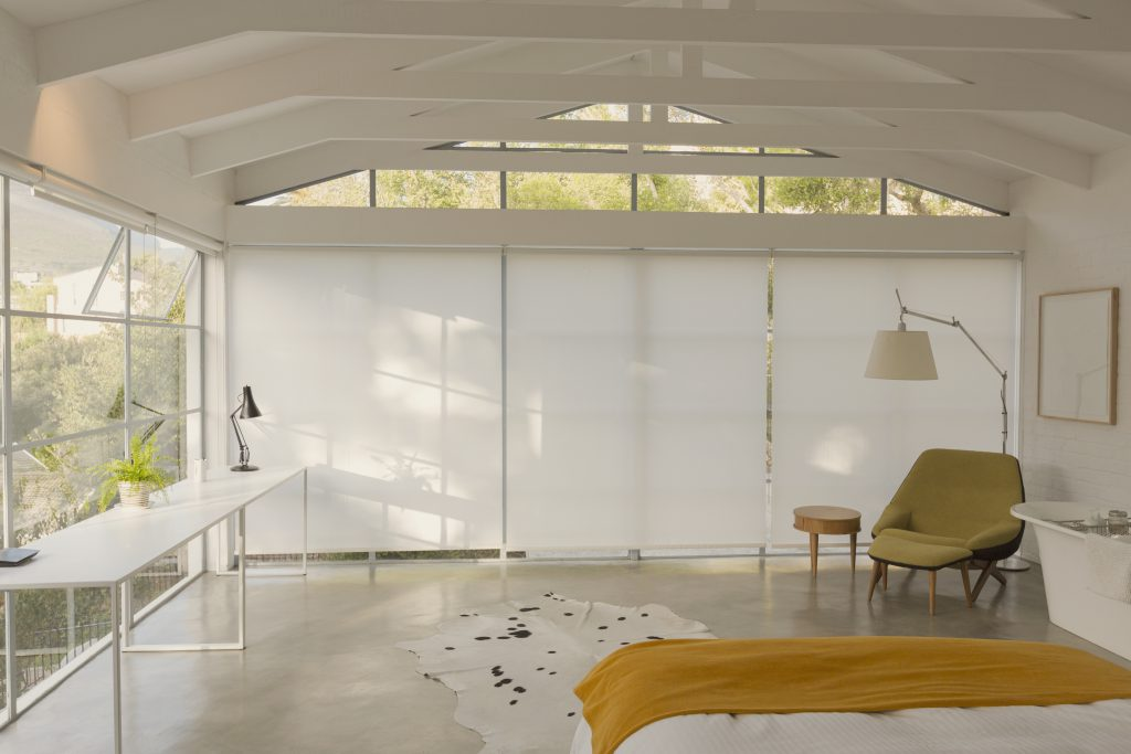An almost all white mid-century modern bedroom featuring a chair and throw in yellow tones.