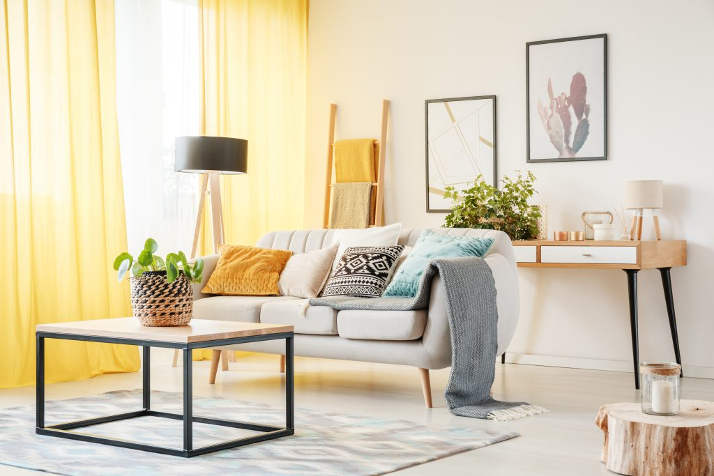 A well lit living room featuring modern yet comfy sofa, a tall lamp, an accent table and a coffee table. Yellow pillows throws and window curtains add a cheerful vibe to this almost all white  living room.