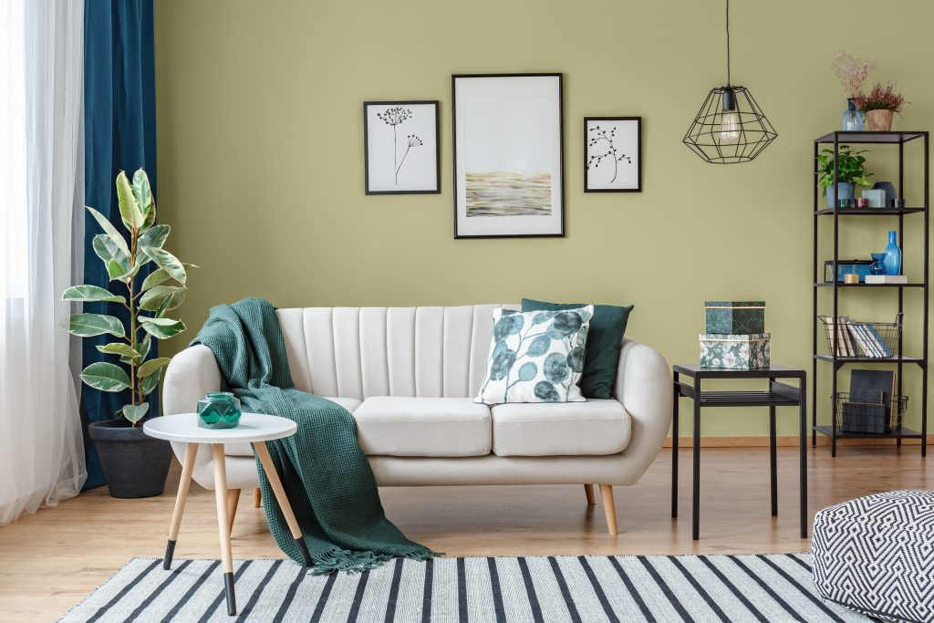 A modern living room painted in green color called Secret Meadow.  A mix of neutral and dark green furniture and decor items.