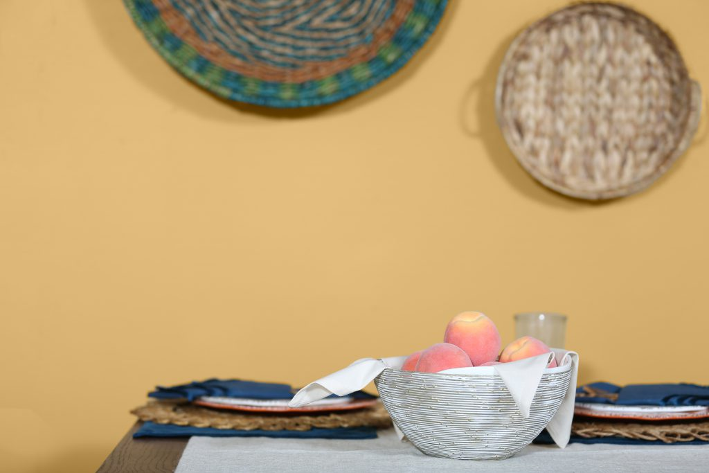 A basket of peaches against a yellow wall painted in charismatic.