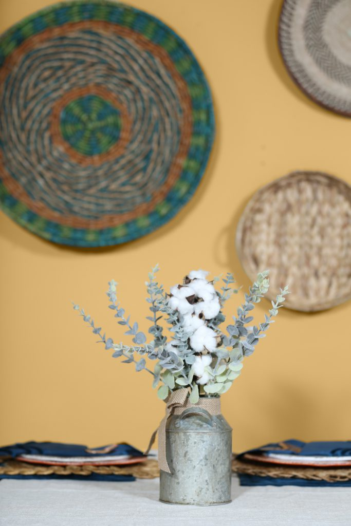 A flower vase on a dining table against a wall painted in Charismatic.