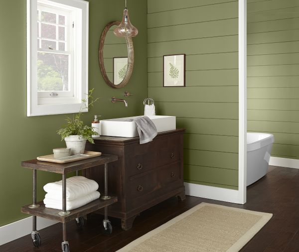 A farmhouse paneled bathroom featuring brown sink cabinet and storage table. Walls are painted in green color called Secret Meadow and trim is painted in a crisp white.