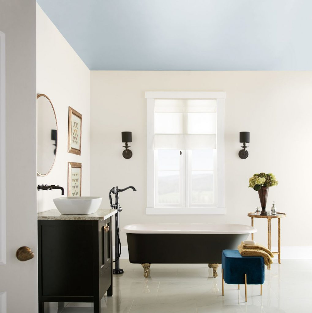 A big bathroom featuring a ceiling painted in a light blue color called Light Drizzle.  A black sick cabinet and a black claw-foot tub, and black oil rubbed bath hardware.