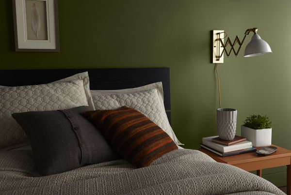 A bedroom painted in dark green color called Secret Meadow.  A bed made with mostly brown, beige and off-white bedding.
