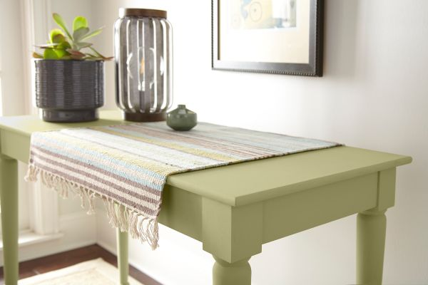 A small accent tale painted in green color called Back to Nature.  Eclectic decor wood, ceramic and textile pieces on top of a table.