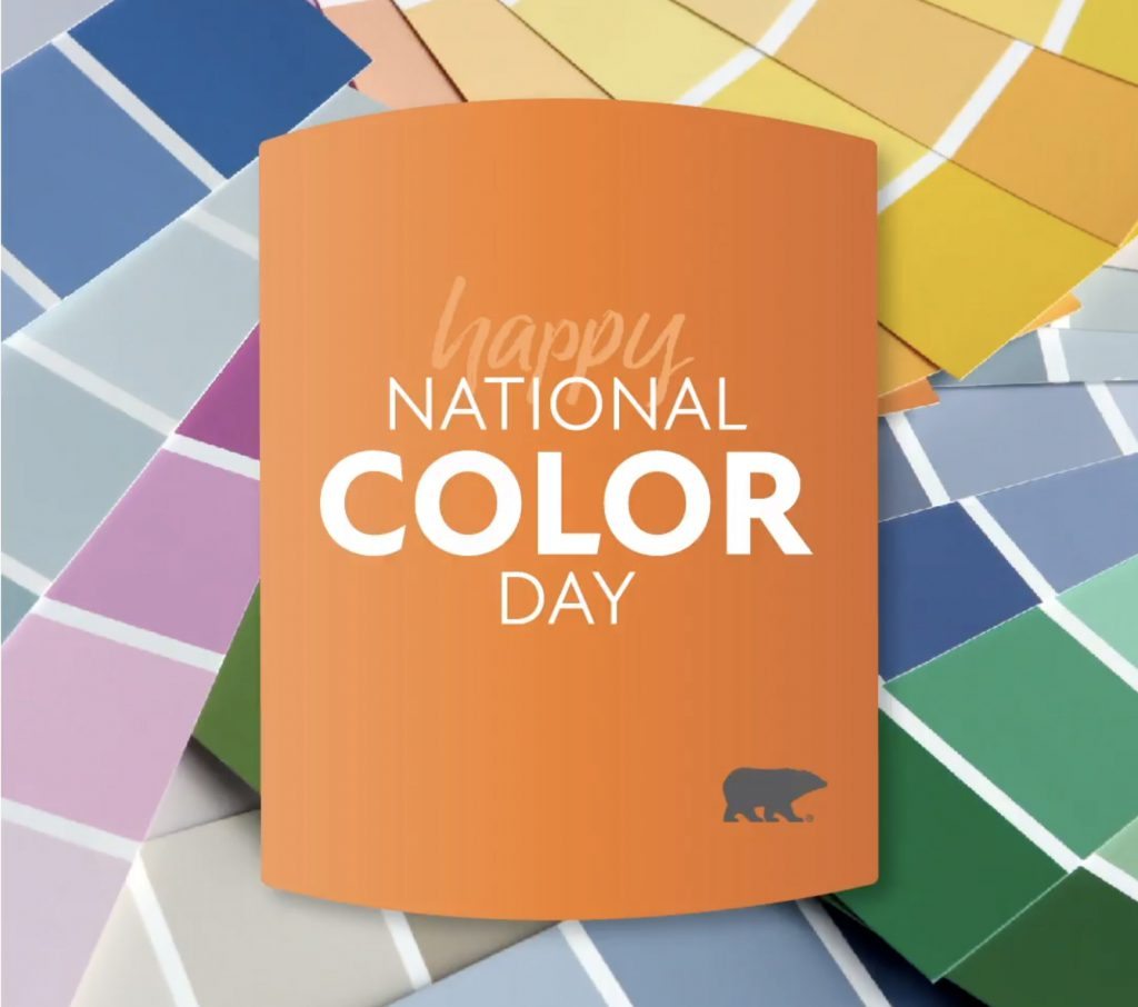 "A variety of different color paint swatches fanned out. On top of them is a chip shape block with the title written on it, ""Happy National Color Day""."