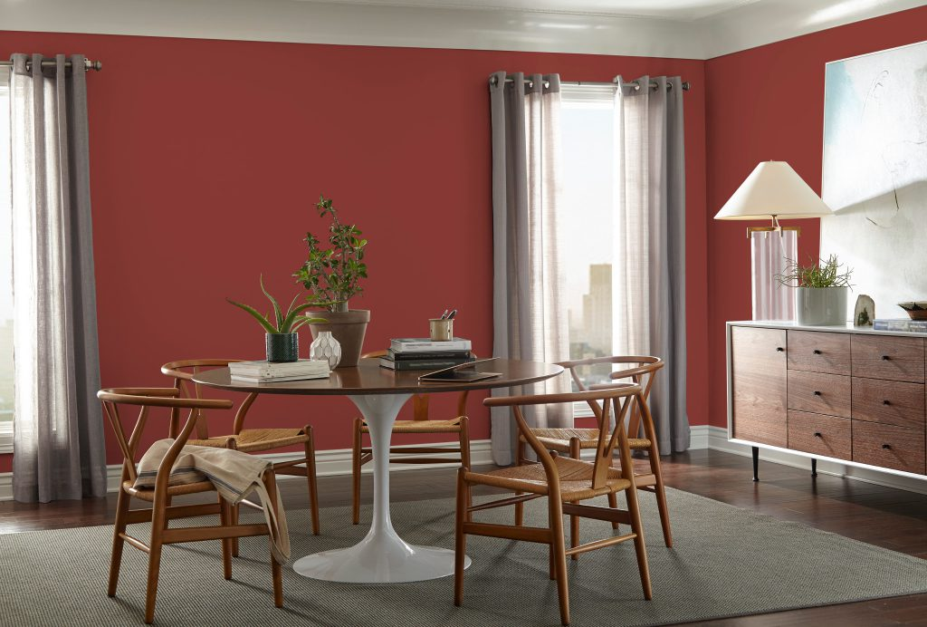 A dining room area featuring eclectic furniture and decorative elements. A mid-century modern buffet table with oversize decorative pieces including a lamp, a potted plant and a large painting. Walls are painted in red color called Red Pepper.