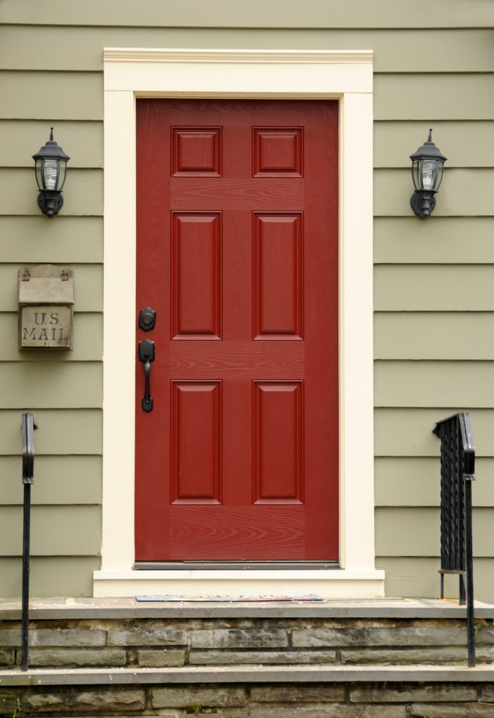 A siding home exterior featuring a main front door painted in a red color called Red Pepper. Metal mailbox mounted on siding wall, wrought iron railings and lamps