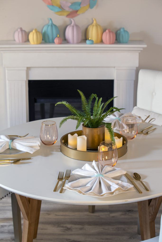 A simple table setting for three featuring gold eating utensils.  A fireplace mantle featuring ceramic pumpkins painted in pastel colors and metallic gold touches.