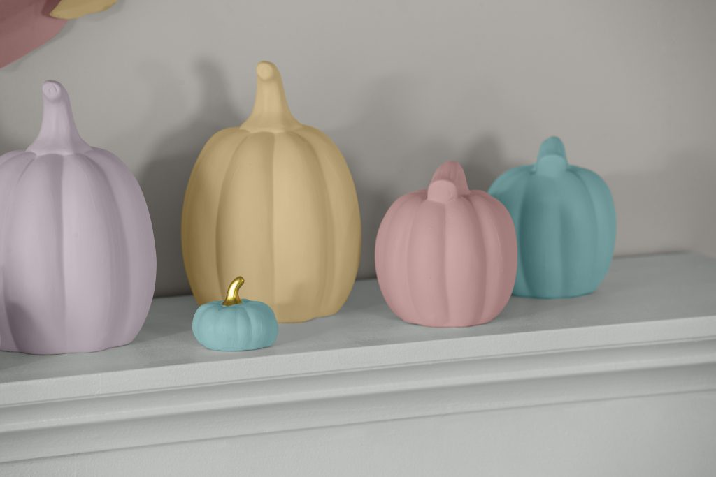 A close up detail image of ceramic pumpkins painted in multi-pastel tones.