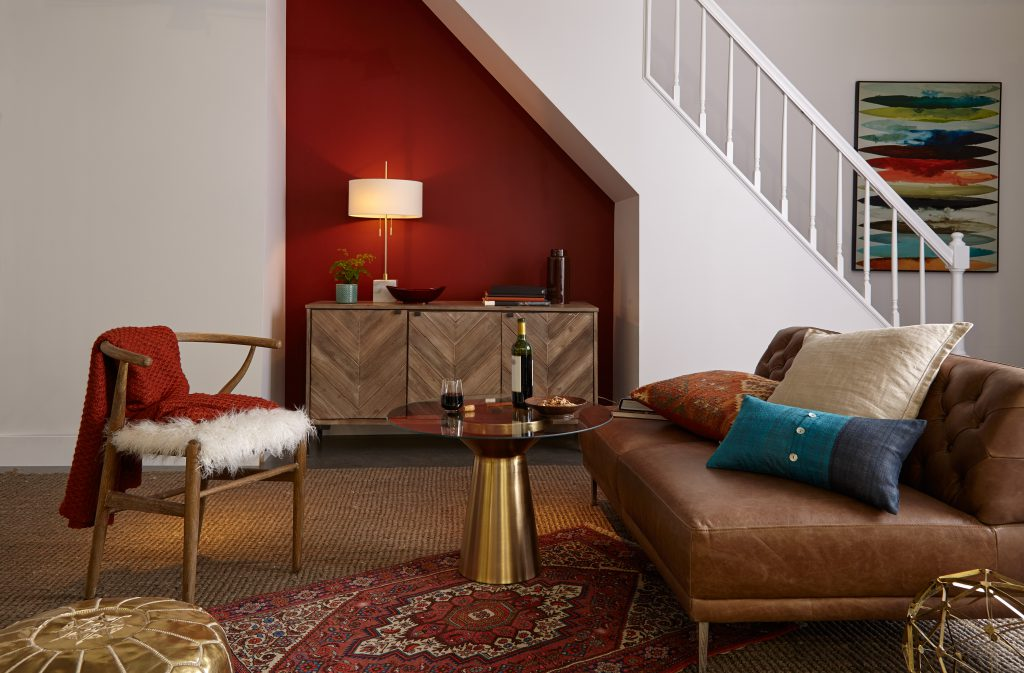 An interior living area featuring a staircase and nook below it, wall painted in red color called Red Pepper. Several eclectic furniture and decorative elements featuring pops of warm red tones.