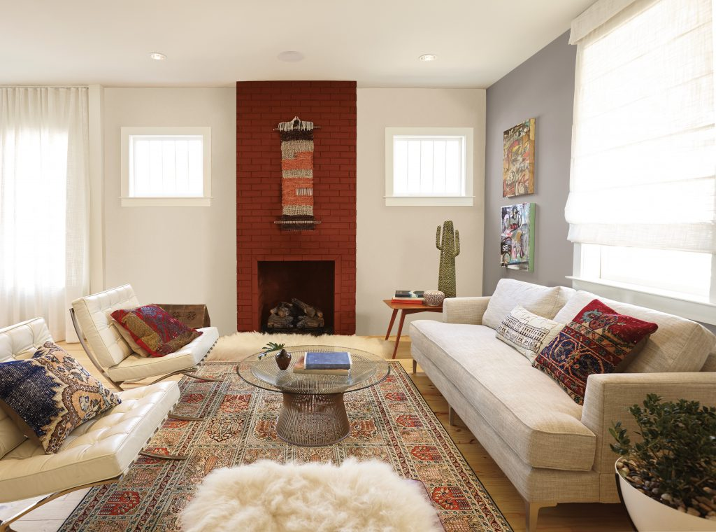 A living room featuring a brick fileplace painted in red color called Red Pepper. A sofa fabric sofa and leather chairs decorated with multi-color pillows.
