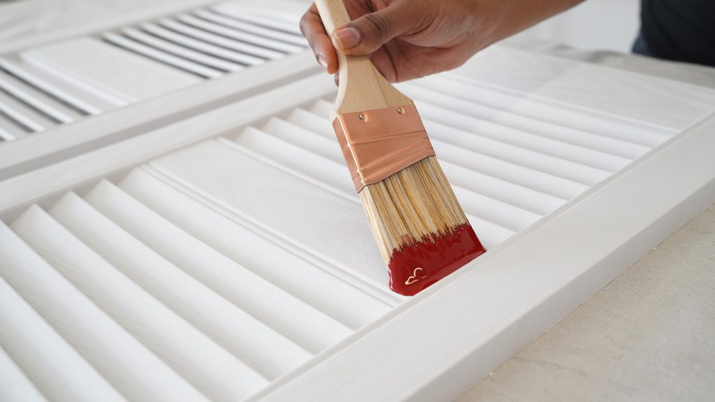 Hand brushing Red Pepper paint over white shutters
