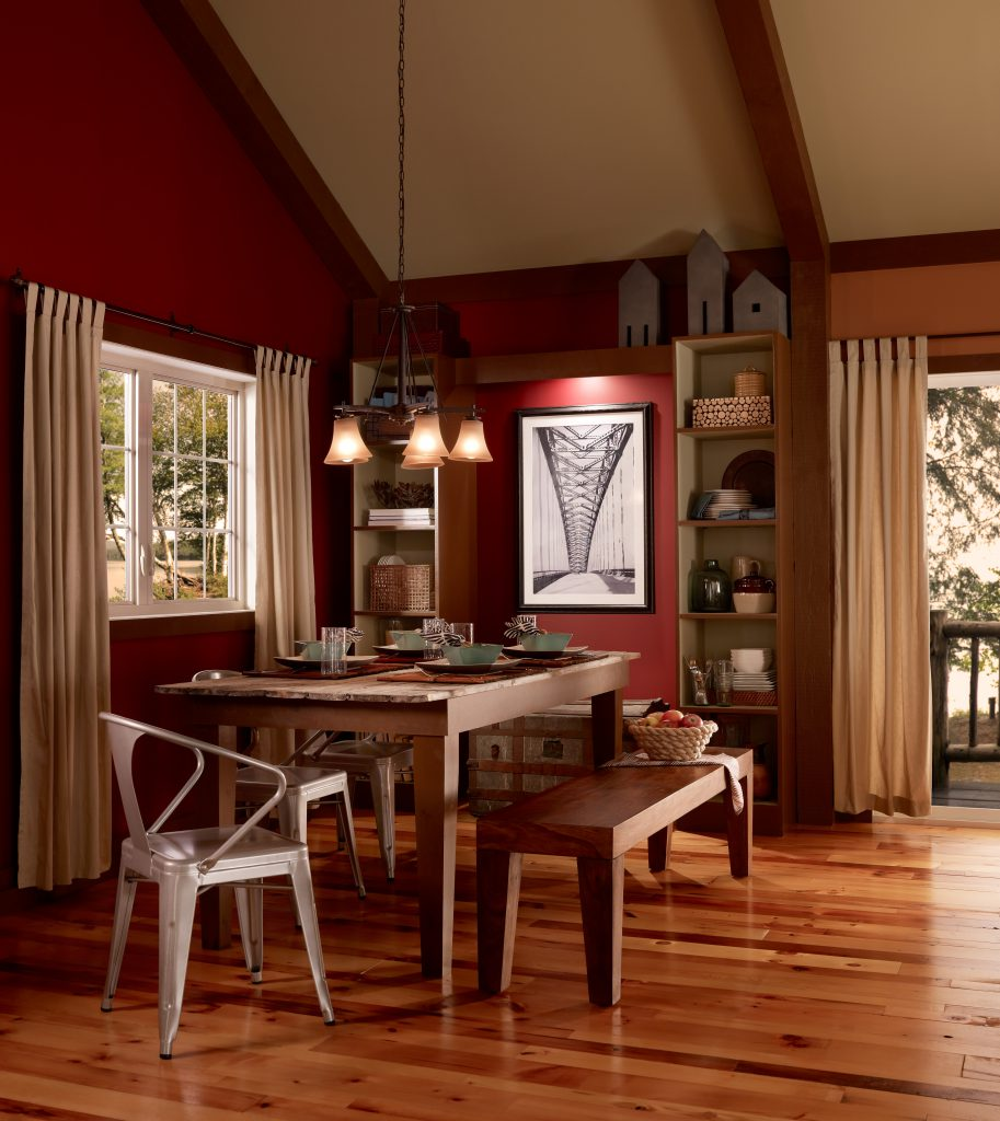 A Craftsman style home interior featuring a dining area with eclectic furniture.  Ceiling with wooden beams. Walls are painted in red color called Red Pepper.