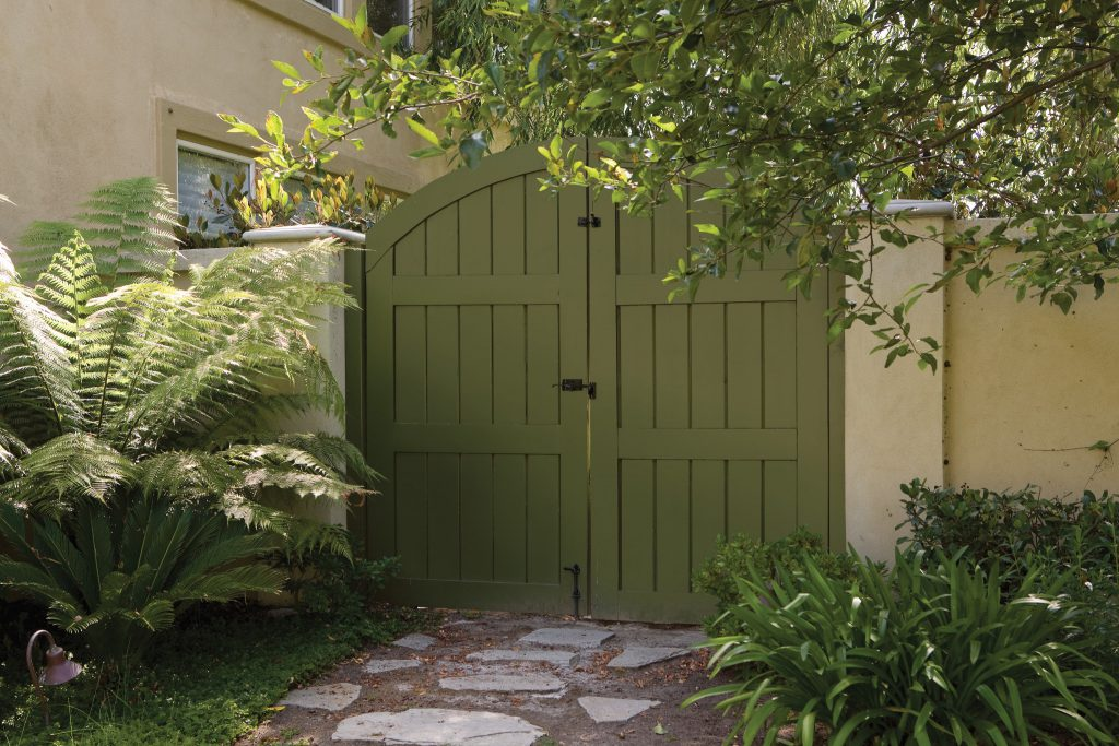 A stucco house fence and wooden gate, the gate is painted in green color Secret Meadow.