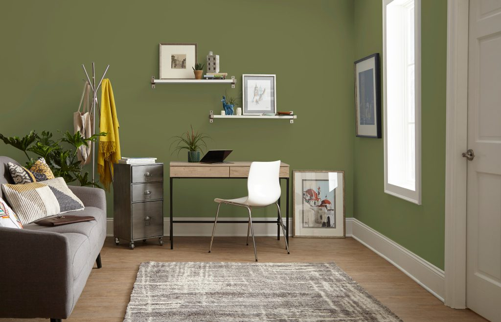 A home office featuring a working area with a desk, chair and small filing cabinet.  A gray sofa with decorative pillow.  The office walls are painted in green color called Secret Meadow and trim is painted in crisp white color called Polar Bear.
