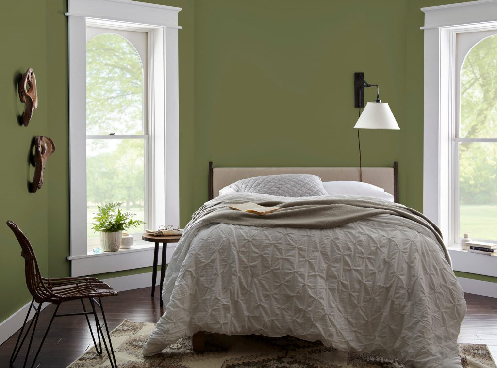 A master bedroom with two windows and bed place in the middle.  Simple and layered neutral bedding. Walls are painted in classic color called Secret Meadow.
