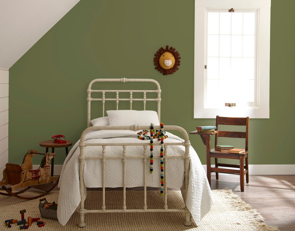 A child's room with a small bed, classic wooden toys and chair-desk.  A wall is painted in green color called Secret Meadow.