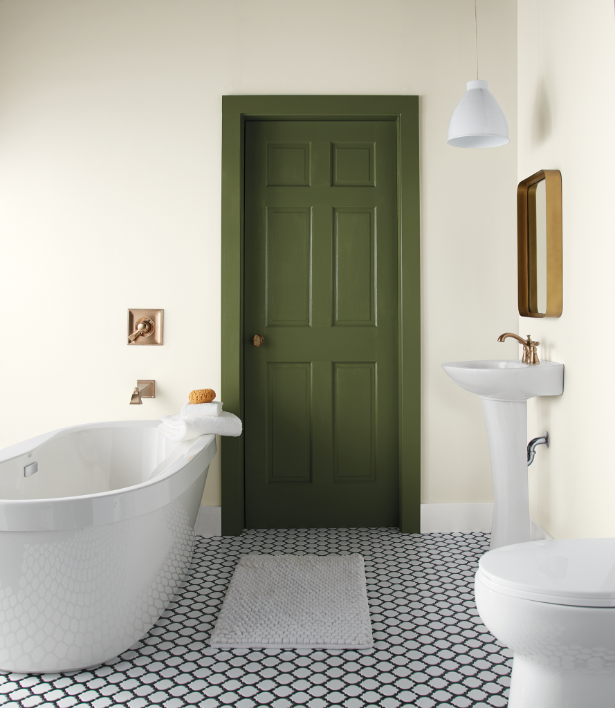 An all white painted bathroom featuring a standalone modern tub and a small sink.  A door and trim painted in green accent color called Secret Meadow.