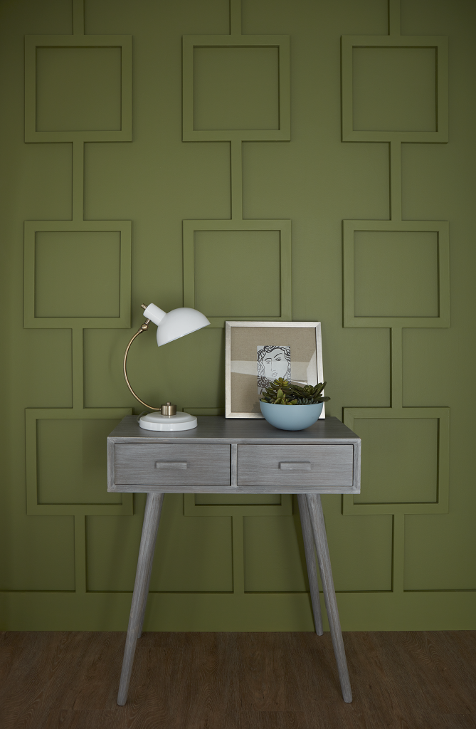 A geometric paneled wall painted with green color called Secret Meadow, there's a small accent table in-front of it.