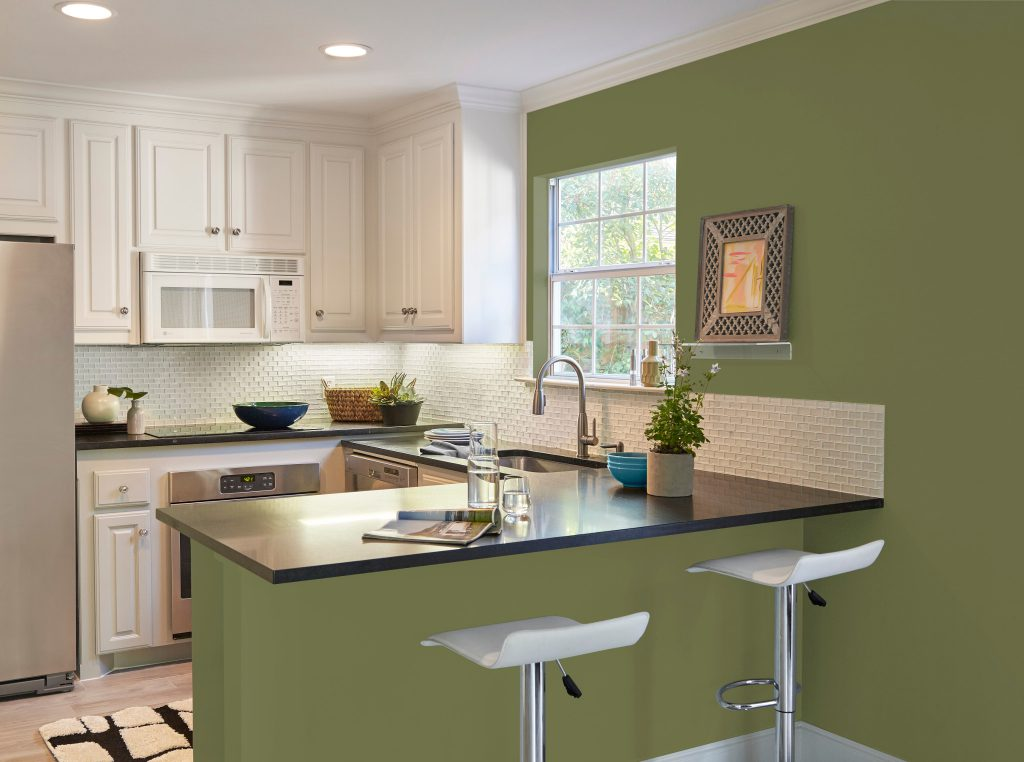 A kitchen area featuring a breakfast bar, white wood cabinets and stainless steel appliances.  The wall is painted in green color called Secret Meadow.
